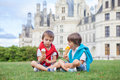 Two adorable boys in casual clothing eating ice cream sitting o on a lawn front of the biggest castle along the loire river Stock Image