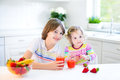 Two adorable kids having fruit for breakfast drinking juice Royalty Free Stock Photo