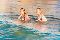 Two adorable kids playing in the sea on a beach happy Stock Photos