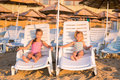 Two adorable kids sunbathing on a beach lounge Royalty Free Stock Image