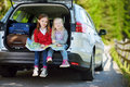 Two adorable little sisters exploring a map before going on vacations with their parents Royalty Free Stock Photo