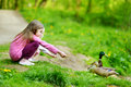 Two adorable sisters feeding ducks by a river Royalty Free Stock Photo