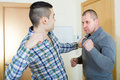 Two adult males having fight indoor Royalty Free Stock Images