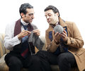 Two adult men mid s mid s wearing old man clothes makeup sitting used up vintage sofa one them knitting other one holding ball Stock Photo