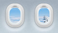 Two airplane or jet windows with wing and sky behind it Stock Image