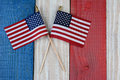 Two american flags on painted wood background a red white and blue surface perfect for fourth of july or memorial day projects Royalty Free Stock Images