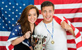 Two american sports fans americans posing as athletes being supporters of their national team holding an flag and a trophy Stock Photo