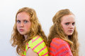 Two angry girls agitated european teenage sitting with backs touching each other Stock Photography