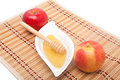 Two apples and honey on a straw kitchen mat Stock Images