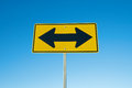 Two arrow road sign in yellow and black points the way to opposite directions Royalty Free Stock Images