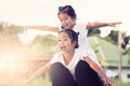 Two asian child girls having fun to fly on mother`s leg Royalty Free Stock Photo