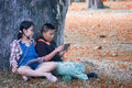 Two Asian children sitting in the garden summer time and play tablet. Royalty Free Stock Photo