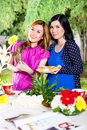 Two asian girlfriends with flowrers stylish cutting flowers and bind them to bouquets in exotic environment Royalty Free Stock Images