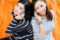 Two asian girlfriends with phone indonesian friends using mobile phones or smartphones Royalty Free Stock Photography