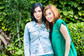 Two asian girlfriends stylish posing in the green and looking in the camera Stock Photos