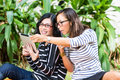 Two asian girlfriends with tablet computer indonesian friends looking on a in a tropical environment Stock Images