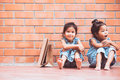 Two Asian girls who feel bored sitting and hugging their knees Royalty Free Stock Photo