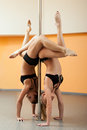 Two athletic girl stand on hands during pole dance Royalty Free Stock Photos
