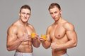 Two athletic men with glasses of orange juice Royalty Free Stock Photo