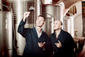 Two attentive men coworkers wearing uniform standing with glass Royalty Free Stock Photo