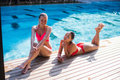 Two attractive blonde and brunette girls with long hair are lying on flor near pool. They wear bikini and swimsuit. They Royalty Free Stock Photo