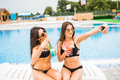 Two attractive brunette women wearing bikini posing near the swimming pool, making selfie photo. Summer time Royalty Free Stock Photo