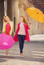 Two attractive girlfreinds with the umbrellas colorful Stock Photo