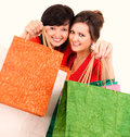 Two attractive girls after shopping holding bags white background Stock Photo