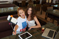 Two attractive ladies best friends posing while making photo with cell telephone camera during rest in restaurant, Royalty Free Stock Photo