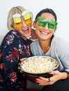 Two attractive woman friends with funny glasses and popcorn women bowl of on the sofa Royalty Free Stock Image