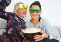 Two attractive woman friends with funny glasses and popcorn women bowl of on the sofa Royalty Free Stock Photo