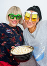 Two attractive woman friends with funny glasses and popcorn women bowl of on the sofa Royalty Free Stock Photography