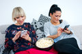 Two attractive woman friends with mobile phone and popcorn women phones on the sofa chating Royalty Free Stock Image