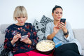 Two attractive woman friends with mobile phone and popcorn women phones on the sofa texting Stock Images