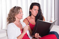 Two attractive woman siiting on couch discussing and taking note women notes Royalty Free Stock Photo
