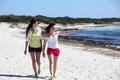 Two attractive woman walking on a beach young women in shorts barefoot tropical in the summer sun pointing out to sea Stock Photo