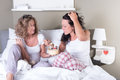 Two attractive women enjoying their women s evening in bed Stock Images