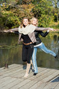 Two attractive women posing by the pond in the autumn park young Royalty Free Stock Images
