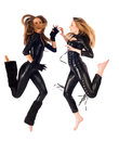 Two attractive young women in cat costumes jumping at white background Stock Photography