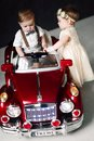 Two babies wedding - boy and girl dressed as bride and groom playing with toy car Royalty Free Stock Photo