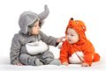 Two baby boys dressed in animal costumes playing over white background Royalty Free Stock Photography