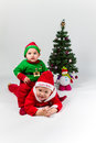 Two baby boys dressed as santa claus and santas he helper lying next to christmas tree white background Stock Photography