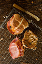 Two Bacon Cross Buns on Wire Rack Beside Butter Knife Royalty Free Stock Photo
