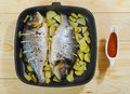 Two baked fish with potato in the pan Stock Image
