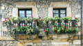 Two balconies with potted plants and flowers located on a old stone façade in the spanish town of comillas north of spain Royalty Free Stock Photography