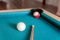 Two balls and a cue on the table Stock Photos