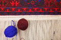 Two balls of yarn on carpet loom Stock Photo