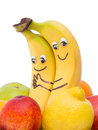 Two bananas with eyes and mouth between other fruit Stock Image