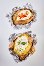 Two barbecued baked potatoes in tin foil Royalty Free Stock Photo