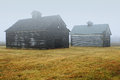 Two barns in fog old grain a field and Stock Photography